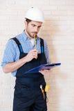 Рабочий-строитель думая о что-то используя доску сзажимом для бумаги Стоковое Изображение RF