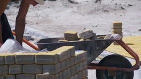Рабочий-строитель управляет тачкой с вымощая камнями на строительной площадке видеоматериал