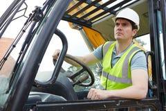 Рабочий-строитель управляя землекопом стоковое фото