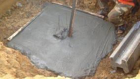 Рабочий-строитель штукатуря вокруг разбивочного учреждения кучи, перед использованием доск штарки и лить бетона для разбивочного