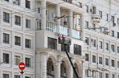2 рабочий-строителя в ведре корабля крана реконструируют фасад здания в Москве Стоковые Изображения RF