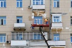 2 рабочий-строителя в ведре корабля крана реконструируют фасад здания в Москве Стоковая Фотография RF