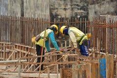 2 рабочий-строителя изготовляя бар подкрепления земного луча стальной Стоковые Изображения