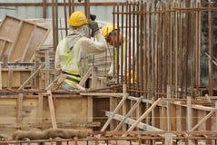 2 рабочий-строителя изготовляя бар подкрепления земного луча стальной Стоковое фото RF