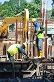 2 рабочий-строителя изготовляя бар подкрепления земного луча стальной Стоковая Фотография