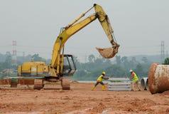 2 рабочий-строителя поднимая бетонную плиту используя экскаватор Стоковые Фото