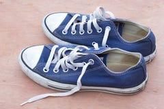 Равенства ботинок холста голубых на деревянной предпосылке, пакостной сини s Стоковые Фото