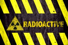 Радиоактивные символ и слово опасности ионизирующего излучения при желтые и черные нашивки покрашенные на массивнейшей бетонной с Стоковые Изображения