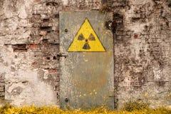 Радиоактивный символ опасности ионизирующего излучения покрашенный на старой массивнейшей заржаветой железной двери Стоковое фото RF