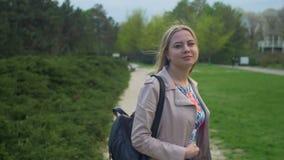 Радостная белокурая девушка поворачивая назад и усмехаясь в парке видеоматериал