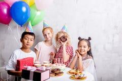 Радостная группа в составе счастливые дети стоя около таблицы стоковое изображение rf