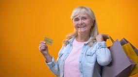 Радостная дама пенсионера показывая хозяйственные сумки и золотую карту, стоя клиент сток-видео