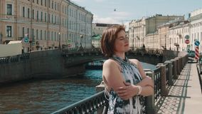 Радостная девушка в запятнанном кресте платья подготовляет около реки в старом центре города видеоматериал