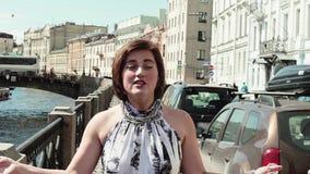 Радостная девушка в запятнанном платье поет на обваловке в старом центре города видеоматериал