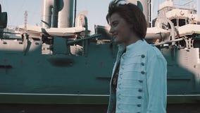Радостная девушка в платье лета усмехаясь перед старым музеем линкора сток-видео