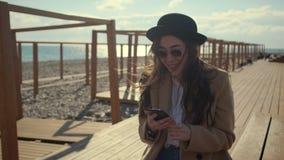 Радостная девушка занимается серфингом интернет смартфоном, сидя в об сток-видео