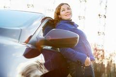 Радостная девушка положенная против автомобиля стоковые изображения rf