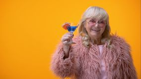Радостная достигшая возраста женщина делая clinking жест с голубым коктейлем к камере, партии сток-видео