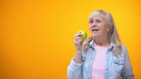Радостная достигшая возраста женщина наслаждаясь вкусом свежего хрустящего яблока, устной заботой, orthodontics сток-видео