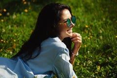 Радостная женщина при солнечные очки очаровательной улыбки нося, лежа на зеленой траве Стоковое Изображение