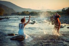Радостная как раз пожененная пара имеет потеху пока брызгающ воду на одине другого во время захода солнца Красивейший ландшафт стоковые фотографии rf