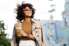 Радостная курчавая женщина усмехаясь и держа чашку сока стоковые изображения rf