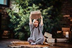 Радостная маленькая девочка с белокурым вьющиеся волосы нося теплый свитер бросает вверх подарочную коробку пока сидящ на поле ря стоковые изображения