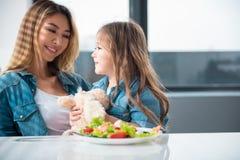 Радостная мать и девушка есть здоровую еду в кухне Стоковые Изображения RF