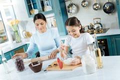 Радостная мать и дочь варя совместно Стоковое Изображение