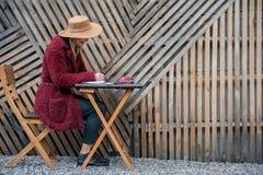 Радостная молодая женщина делая примечания в сочинительств-пусковой площадке Стоковая Фотография RF