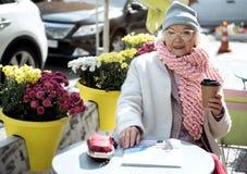 Радостная пожилая женщина расслабляющая вне уютной столовой Стоковое Изображение