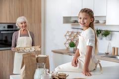 Радостная старуха обрабатывая ее внучку сладостным печеньем Стоковое Изображение RF