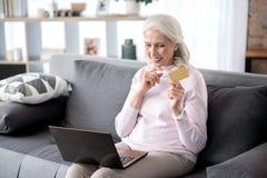 Радостная старшая дама покупая в интернете кредитной карточкой Стоковая Фотография RF