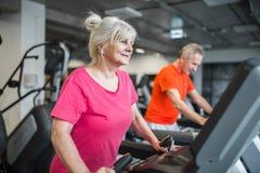 Радостная старшая тренировка дамы на третбане на спортзале Стоковые Фото