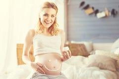 Радостная усмехаясь беременная женщина отдыхая дома Стоковые Фотографии RF