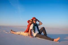 Радостное усаживание пар, спина к спине, в пустыне против голубого Стоковое Изображение