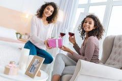 Радостные дамы обменивая подарки и выпивая красное вино Стоковые Фотографии RF