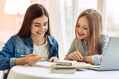Радостные девушки делая домашнее назначение совместно Стоковые Фотографии RF