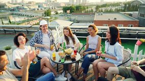 Радостные друзья кладут руки совместно после этого поднимая в воздух сидя в круге на таблице на крыше и выпивать акции видеоматериалы