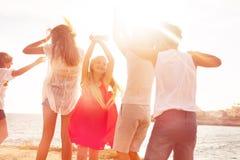 Радостные друзья танцуя на пляже во время захода солнца стоковые изображения