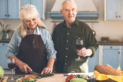 Радостные зрелые пары подготавливая салат совместно дома Стоковое фото RF