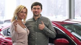 Радостные зрелые пары показывая ключи и большие пальцы руки автомобиля вверх после покупать новый автомобиль стоковое фото rf