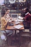 Радостные 3 коллеги сотрудничая на кафе Стоковая Фотография