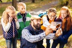 Радостные милые дети стоя за их учителем стоковое изображение rf