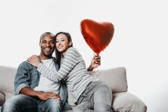 Радостные мужчина и женщина в влюбленности сидя в объятии Стоковое фото RF
