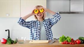 Радостные очаровательные танцы маленькой девочки держа свежий желтый перец на глазах во время варить здоровую еду акции видеоматериалы