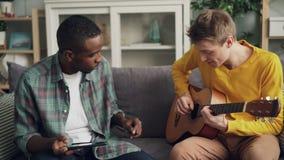 Радостные парни афроамериканец и кавказские друзья играют гитару, используя планшет и смеясь ослаблять на софе акции видеоматериалы