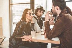 Радостные парни и девушки говоря в кофейне Стоковое Фото