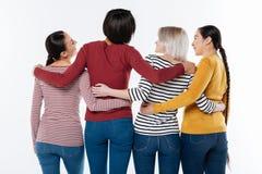 Радостные положительные женщины обнимая один другого Стоковая Фотография