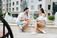 Радостные положительные пары сидя около фонтана Стоковая Фотография